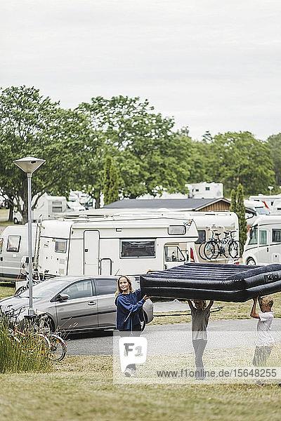 Kinder  die zusammen eine aufblasbare Matratze tragen  während sie auf dem Campingplatz gegen Anhänger laufen