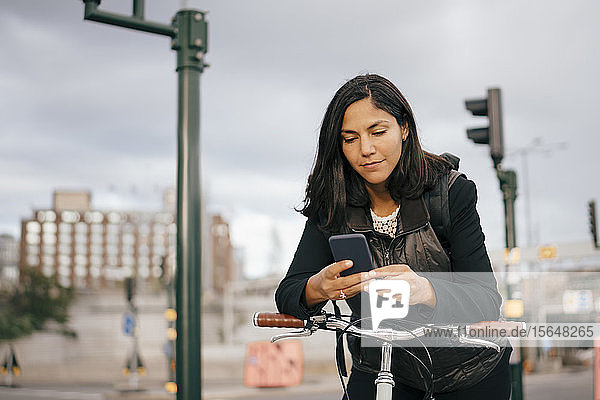 Businesswoman using mobile phone while leaning on bicycle handle in city