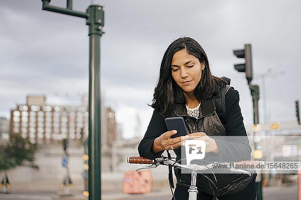 Geschäftsfrau benutzt Mobiltelefon  während sie in der Stadt am Fahrradgriff lehnt