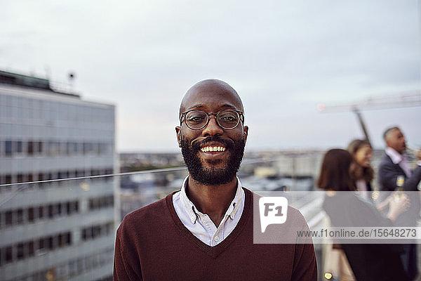 Portrait of smiling businessman wearing eyeglasses enjoying at office party