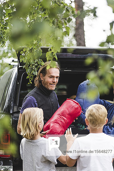 Smiling father giving luggage to children while unloading from car