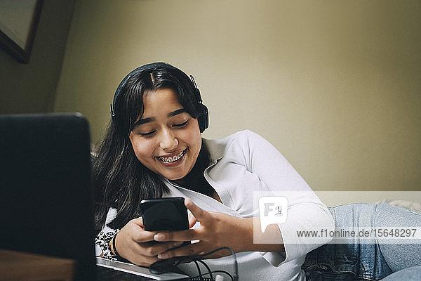 Lächelndes Teenager-Mädchen benutzt Mobiltelefon und Laptop  während es zu Hause im Bett liegt
