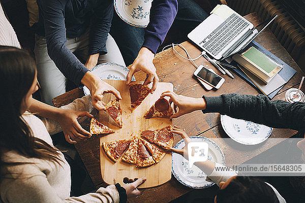 Schrägaufnahme von Freunden  die am Esstisch Pizzastücke nehmen