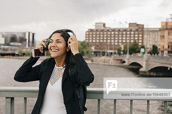 Lächelnde Geschäftsfrau mit Kopfhörern  die auf einer Brücke in der Stadt steht
