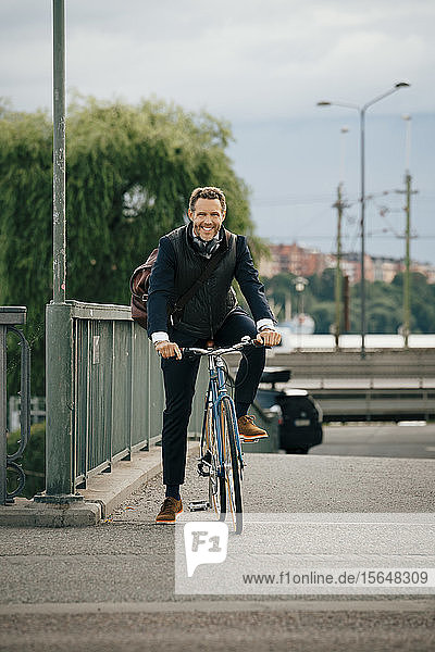 Portrait of smiling businessman riding bicycle on bridge in city