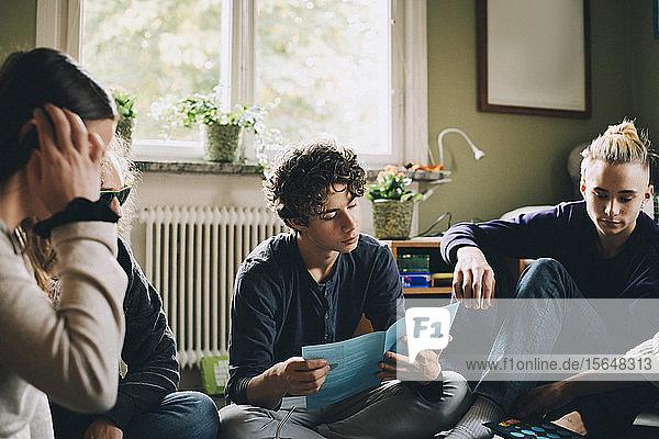 Teenager Junge liest Broschüre  während er mit Freunden im Schlafzimmer sitzt