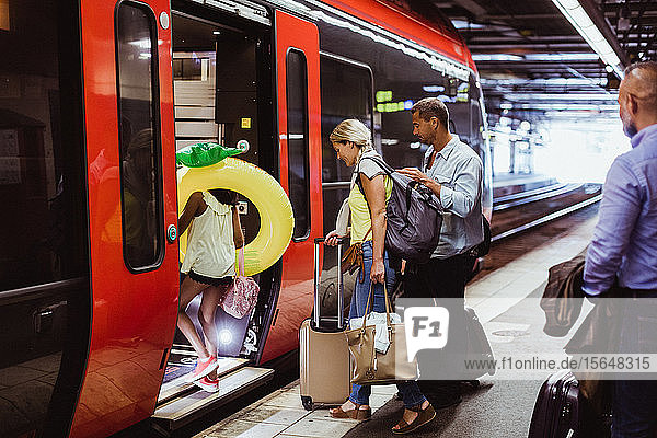 Family with luggage boarding train together at railroad station platform