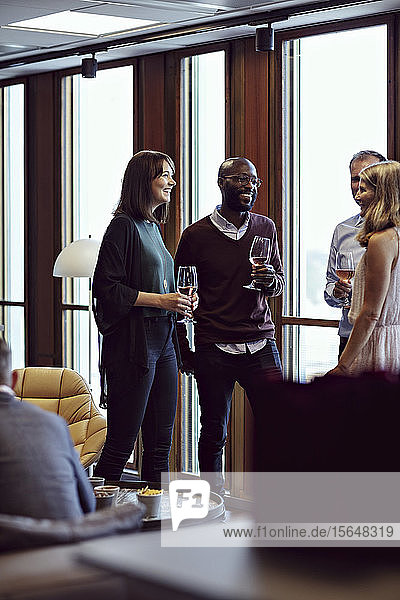 Smiling business professionals discussing over drinks during conference at office