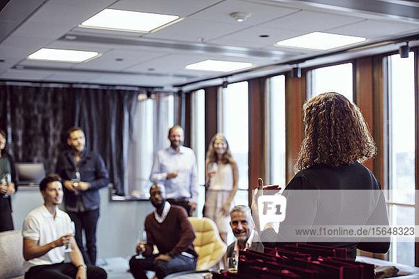 Geschäftsfrau hält Rede vor Mitarbeitern während Büroparty nach der Arbeit