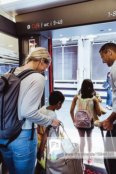 Familie mit Gepäck steigt gemeinsam aus dem Zug