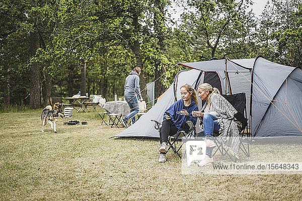Mutter und Tochter beim Kaffee trinken  während sie auf dem Campingplatz ein Handy anschauen