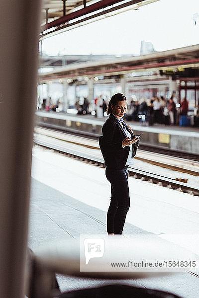 Geschäftsfrau benutzt Mobiltelefon  während sie am Bahnsteig des Bahnhofs steht