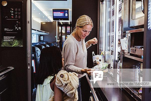 Mutter steht mit ihrer Tochter im Zugkühlschrank und sieht sich Lebensmittel an