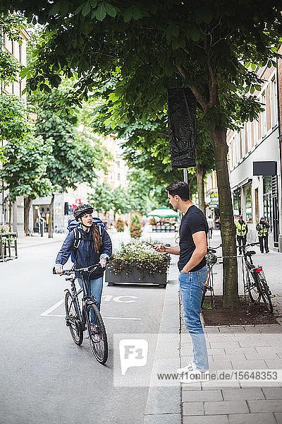 Entbinderin im Gespräch mit männlichem Kunden  der auf dem Bürgersteig steht