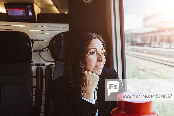 Nachdenkliche Geschäftsfrau schaut durch Fenster  während sie im Zug reist