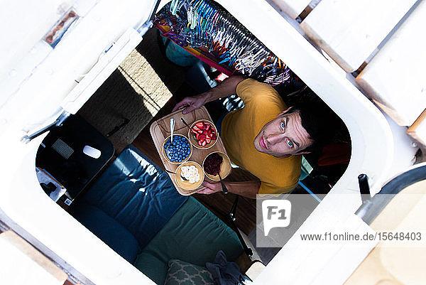 Blick vom Sonnendach des Wohnmobils eines Mannes mit Tablett mit frischen Früchten