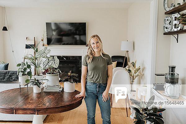 Porträt einer Frau in einem Raum voller Zimmerpflanzen