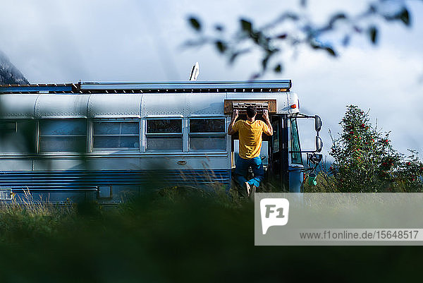 Man doing chin up on exterior of motorhome