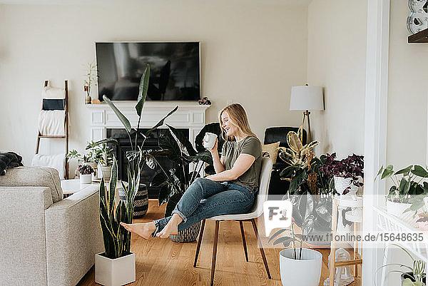 Frau entspannt sich mit einem warmen Getränk in einem Raum voller Zimmerpflanzen