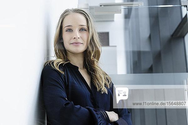 Junge Geschäftsfrau lehnt an weißer Wand in Bürogebäude