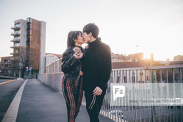 Trendy couple kissing on bridge  Milan  Italy