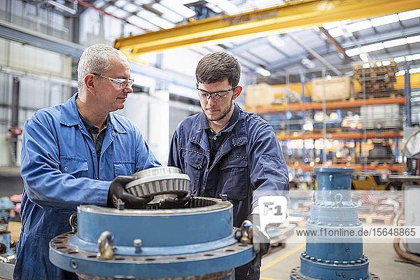 Ingenieur und Lehrling beim Einbau von Lagern in das Pumpenhaus einer elektrotechnischen Fabrik
