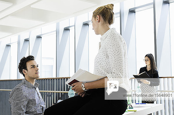 Businessman and businesswoman talking in office  colleague in background