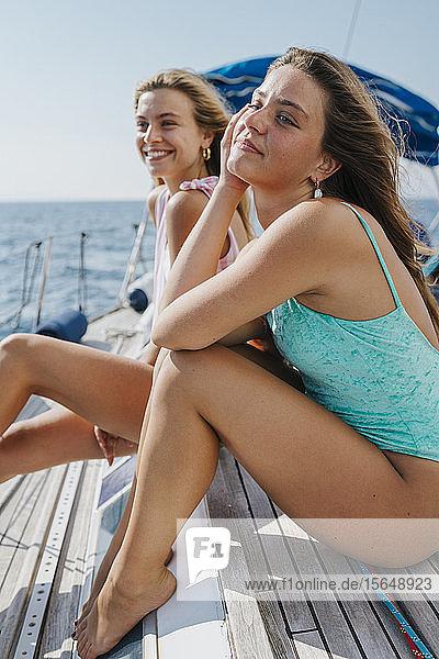 Freunde sitzen an Deck eines Segelbootes und genießen Sonne und Wind  Italien