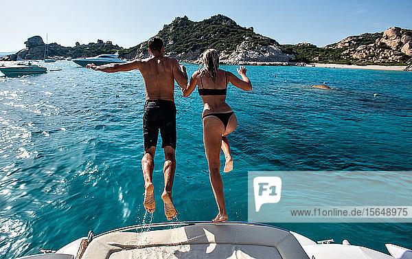 Junges Paar springt von einer Yacht ins Meer  Insel La Maddalena  Sardinien  Italien