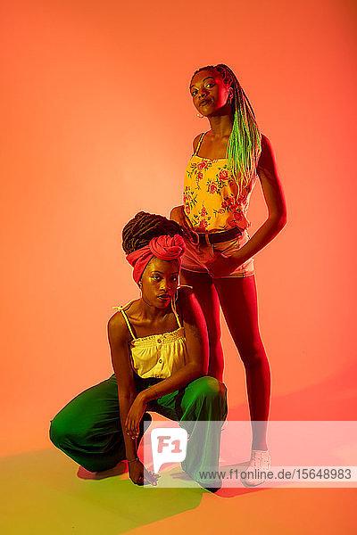 Freunde posieren vor orangem Hintergrund