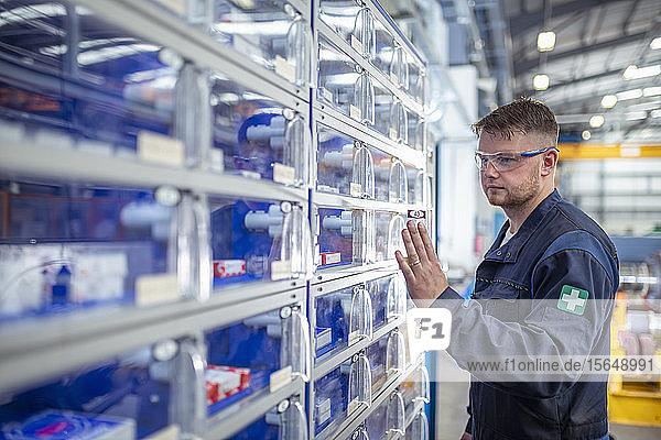 Ingenieur bei der Bedienung eines Werkzeug- und Teileautomaten in einer elektrotechnischen Fabrik