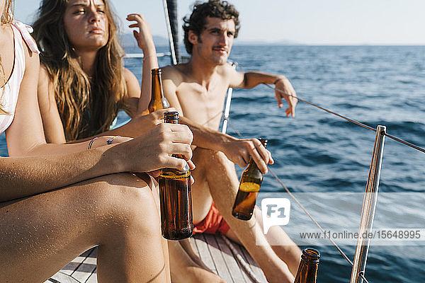 Freunde genießen Bier auf einem Segelboot  Italien