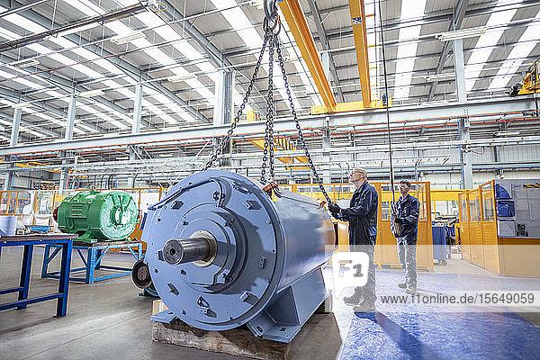 Ingenieure kranen den Generator auf den Prüfstand in einer elektrotechnischen Fabrik