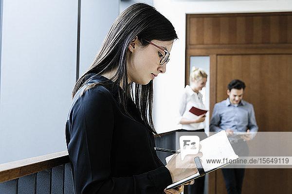 Junge Geschäftsfrau schreibt im Büro Notizen  Kollegen sprechen im Hintergrund