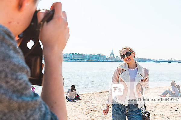 Friends taking photograph on beach  Saint Petersburg  Russia