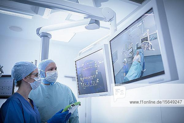 Krankenschwester und Chirurg inspizieren Bildschirme im Operationssaal im Krankenhaus
