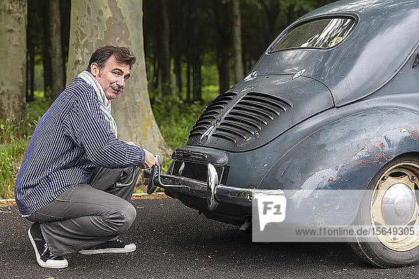 Man fixing vintage car on country road