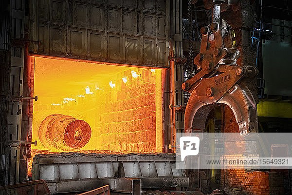 Heat treated red hot steel ingot being lifted by crane in furnace in steelworks