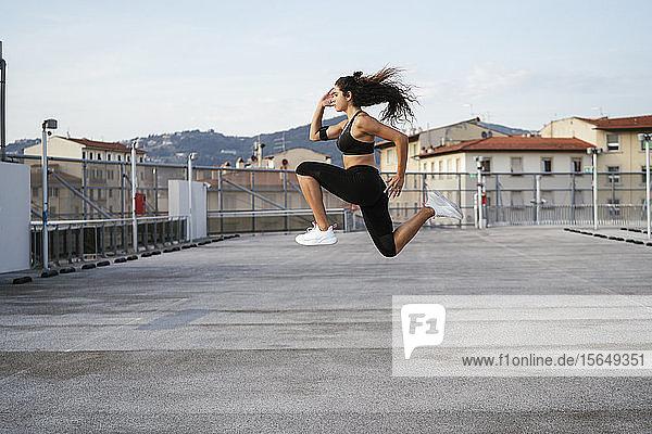 Junge Frau macht Sprungübungen auf dem Dach