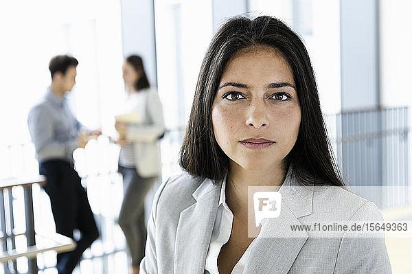Junge Geschäftsfrau im Amt  Kollegen sprechen im Hintergrund