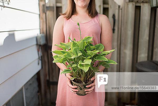 Frau mit Topfpflanze im Garten