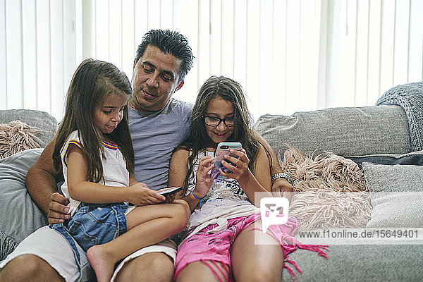 Father watching daughters play computer games on cellphone