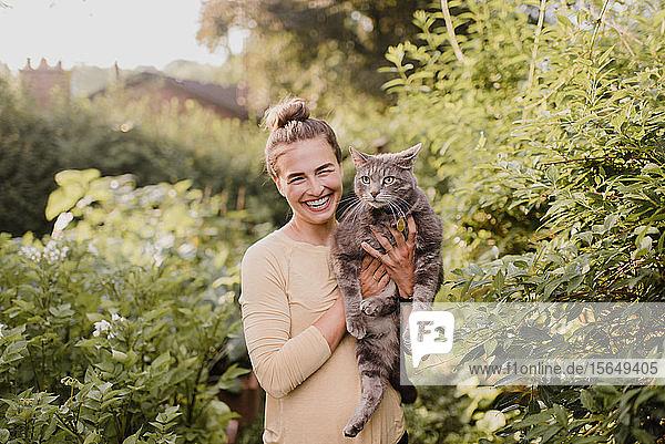 Gärtnerin trägt Katze im Garten
