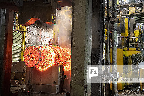 Red hot steel ingot in steel press in steelworks