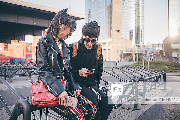 Junges Paar benutzt Mobiltelefon auf Fahrradständern  Mailand  Italien