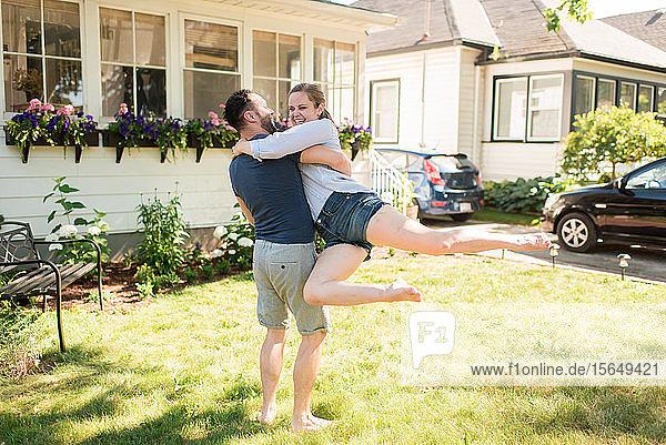 Mann trägt Frau und schaukelt sie im Garten