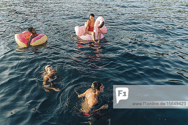 Friends swimming and relaxing on floats on sea  Italy
