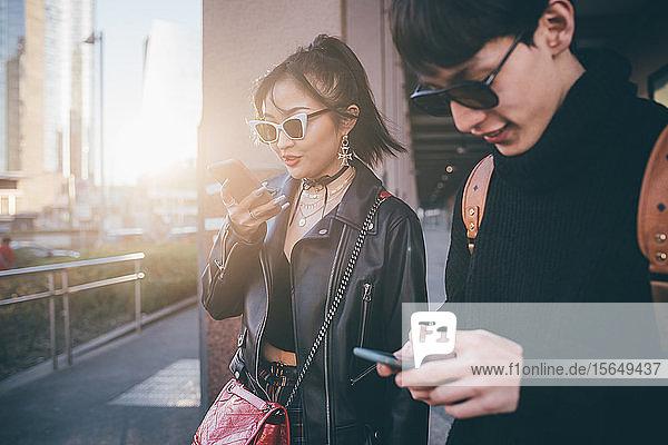 Junges Paar benutzt Mobiltelefon beim Gehen auf der Straße  Mailand  Italien