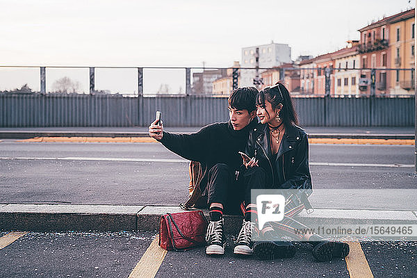 Young couple taking selfie on kerb  Milan  Italy