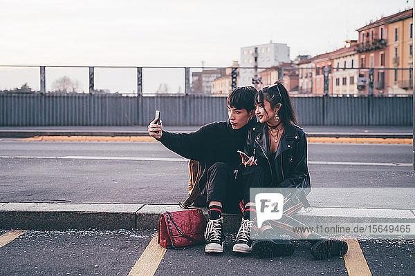 Junges Paar  das sich auf dem Bordstein vergnügt  Mailand  Italien